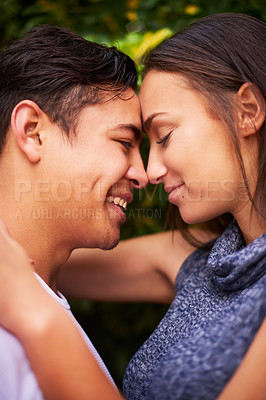 Buy stock photo Closeup shot of a smiling young couple embracing face to face outside