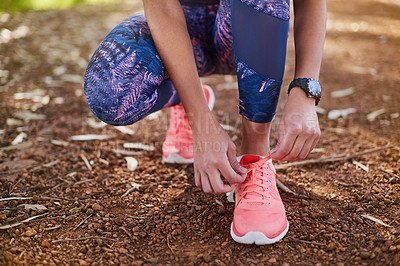 Buy stock photo Cropped shot of a young woman tying her shoelaces before a run