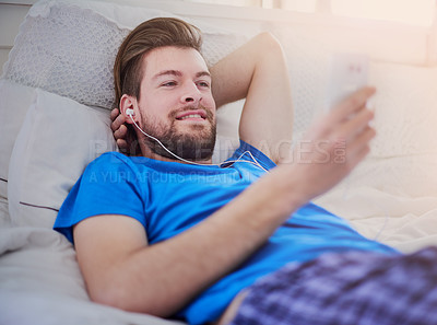 Buy stock photo Cropped shot of a handsome young man listening to music while lying on his bed at home