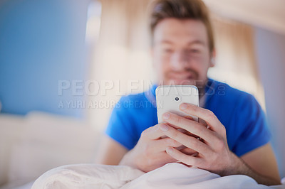 Buy stock photo Cropped shot of a young man texting on his cellphone while lying on his bed