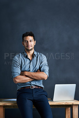 Buy stock photo Portrait of a handsome young businessman standing in front of a desk against a dark background