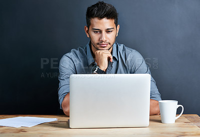 Buy stock photo Cropped shot of a handsome young businessman working on his laptop against a dark background