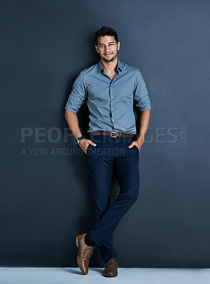 Buy stock photo Studio portrait of a confident young businessman posing against a dark background