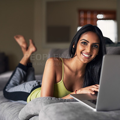 Buy stock photo Portrait of an attractive young woman surfing the net while lying on her sofa at home