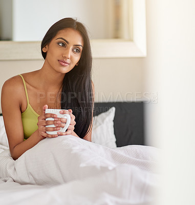 Buy stock photo Shot of a thoughtful young woman having her morning coffee in bed