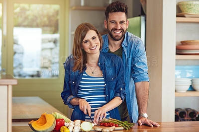 Buy stock photo Portrait of a happy young couple preparing a healthy meal together at home