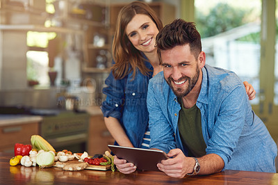 Buy stock photo Portrait of a happy young couple using a digital tablet while preparing a healthy meal together at home