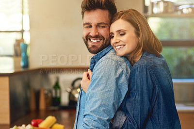 Buy stock photo Shot of a happy young couple sharing an affectionate moment in the kitchen at home