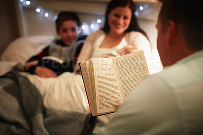 Buy stock photo Cropped shot of a father reading a bedtime story to his wife and son