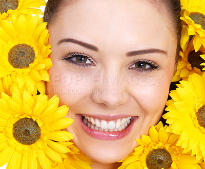 Buy stock photo Beautiful portrait of a young woman surrounded by yellow flowers.