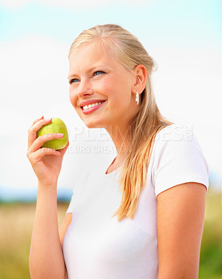 Buy stock photo Pretty young female holding a green apple out in the meadow