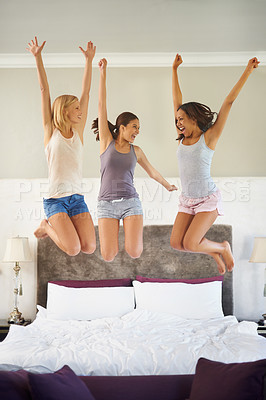 Buy stock photo Three beautiful young women looking happy while jumping on a bed