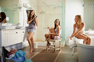 Buy stock photo Shot of three beautiful young women getting ready in the bathroom