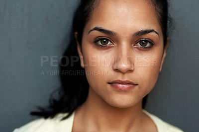 Buy stock photo Closeup portrait of an attractive young Indian woman looking at you against grey background