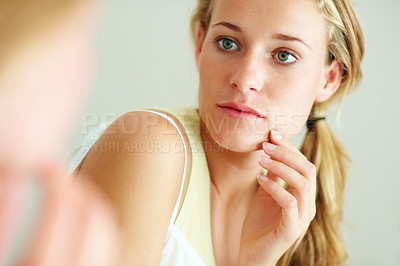 Buy stock photo Closeup portrait of a lovely young woman looking her face in mirror