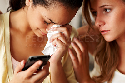 Buy stock photo Closeup portrait of a young woman holding a mobile phone in sorrow with a friend consoling her