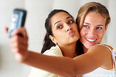 Buy stock photo Happy young women making funny face while taking pictures of themselves through cellphone