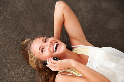Buy stock photo Portrait of an excited young woman speaking on cellphone while lying on the floor