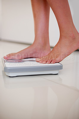 Buy stock photo Lower section legs of a young woman measuring her weight while standing on weighing machine