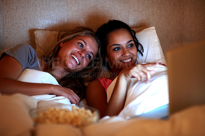 Buy stock photo Portrait of charming young women watching interesting movie on laptop while lying on the bed