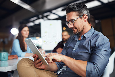 Buy stock photo Shot of a man sitting at a table in an office using a digital tablet with colleagues working in the background