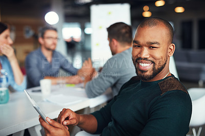 Buy stock photo Portrait of a man sitting at a table in an office using a digital tablet with colleagues working in the background