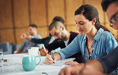 Buy stock photo Shot of a group of colleagues working together at a table in an office
