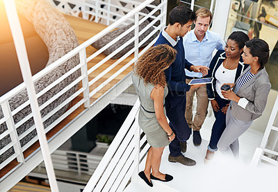 Buy stock photo Shot of a group of coworkers having a meeting in a stairwell in a modern office