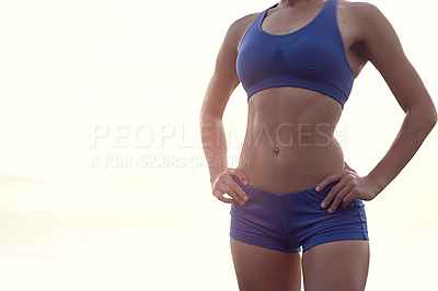 Buy stock photo Cropped shot of a fit woman in sports clothing showing off her toned body proudly