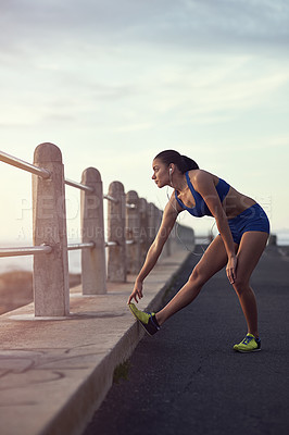Buy stock photo Shot of a fit young woman warming up during her workout outdoors