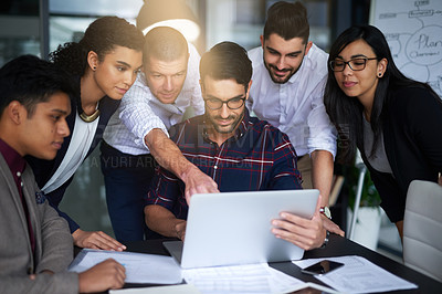 Buy stock photo Shot of a group of colleagues working together around a laptop in an office