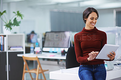 Buy stock photo Shot of a happy young businesswoman using her tablet while standing in the office