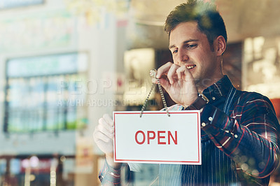 Buy stock photo Shot of a young man hanging up an open sign in a shop window