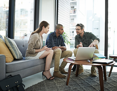 Buy stock photo Shot of a group of colleagues using a laptop during a meeting at work