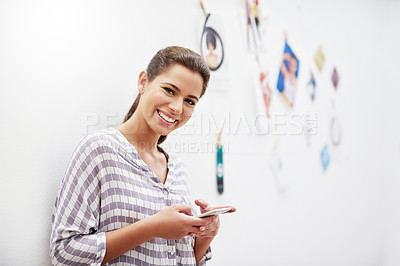 Buy stock photo Portrait of an attractive young designer sending a text while standing in her studio