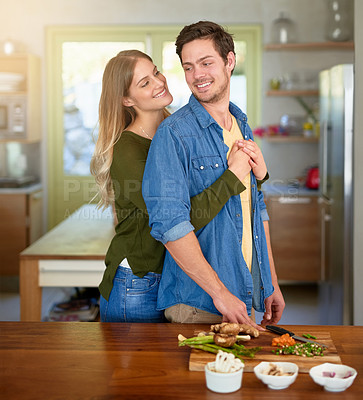 Buy stock photo Shot of an affectionate young couple standing at their kitchen counter chopping up ingredients together for dinner