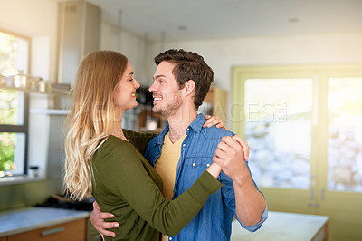 Buy stock photo Shot of an affectionate young couple dancing hand in hand together in their kitchen