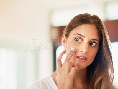 Buy stock photo Cropped shot of a young woman applying moisturiser to her face