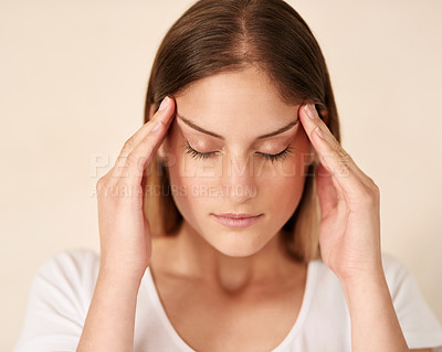Buy stock photo Cropped shot of a young woman experiencing a headache