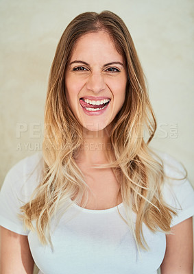 Buy stock photo Portrait of an attractive young woman sticking out her tongue