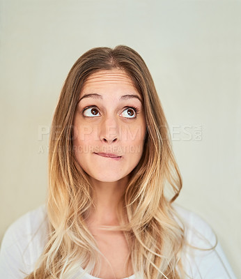 Buy stock photo Cropped shot of an attractive young woman biting her lip in studio