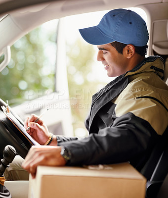 Buy stock photo Cropped shot of a delivery man writing on a clipboard while sitting in his van