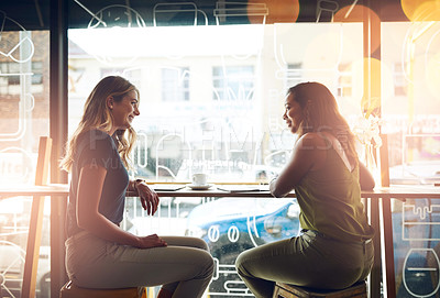 Buy stock photo Shot of two young women at a cafe