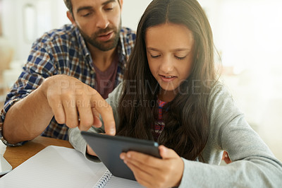 Buy stock photo Shot of a father helping his daughter complete her homework on a digital tablet