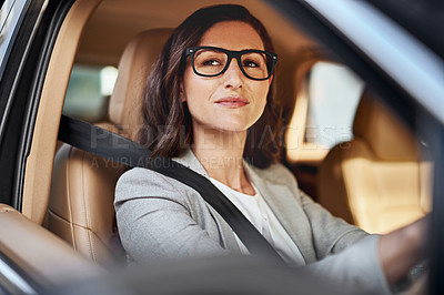 Buy stock photo Shot of a beautiful businesswoman driving to work in her car