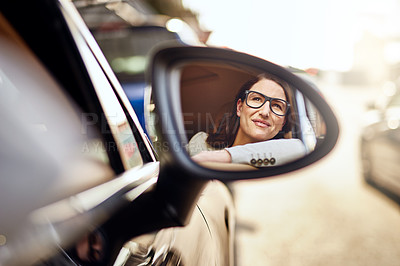 Buy stock photo Shot of a beautiful businesswoman looking in her rearview mirror while driving to work