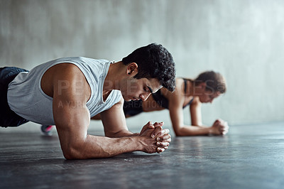 Buy stock photo Shot of two young athletes planking in the gym