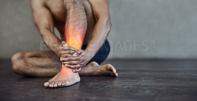 Buy stock photo Shot of an unrecognizable man holding his ankle in pain