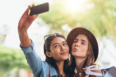 Buy stock photo Shot of two friends taking selfies together while out for a day of shopping