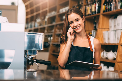 Buy stock photo Shot of a happy young barista using a digital tablet and phone at her cafe